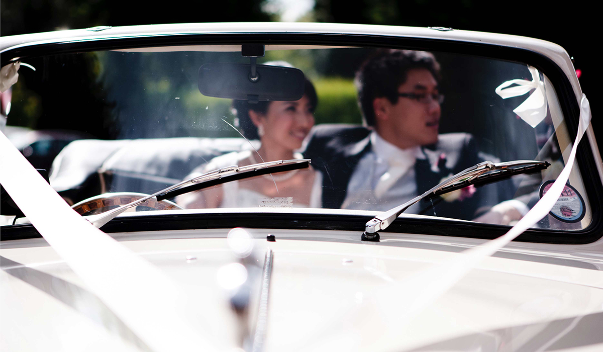 Chinese couple arriving in white Roll Royce